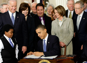 President Obama signs the mis-named Affordable Care Act in 2010. Many of these happy Democrats may not be so happy after the upcoming election.